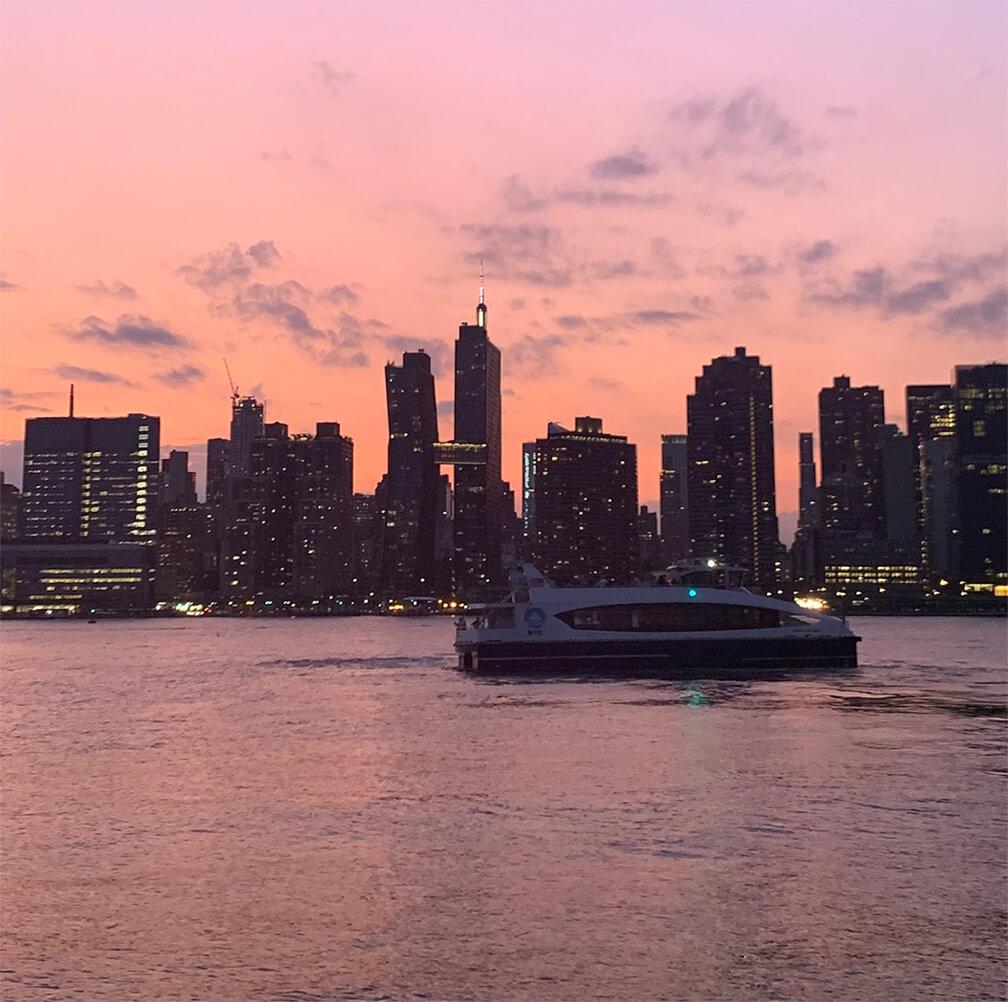NYC Ferry navegando al frente al edificio American Cooper