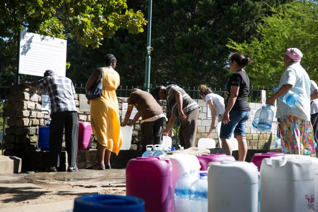 Personas en fila para recoger agua en los puntos de servicio de Ciudad del Cabo