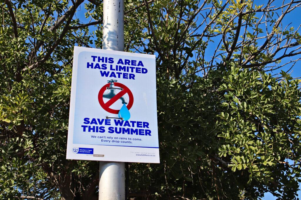 Poste con anuncio de zona de escasez de agua en Ciudad del Cabo